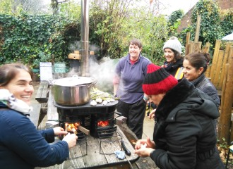 Four people cooking on the Ecozoom La Plancha stove